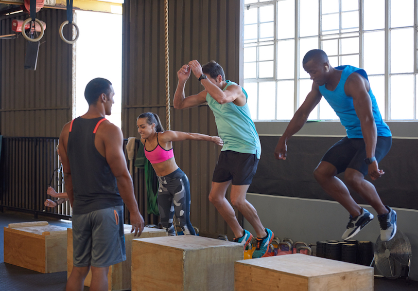 Group of people doing box jumps in a Crossfit-style class