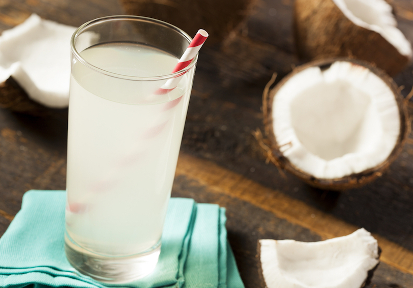 Coconut water in a glass next to open coconut