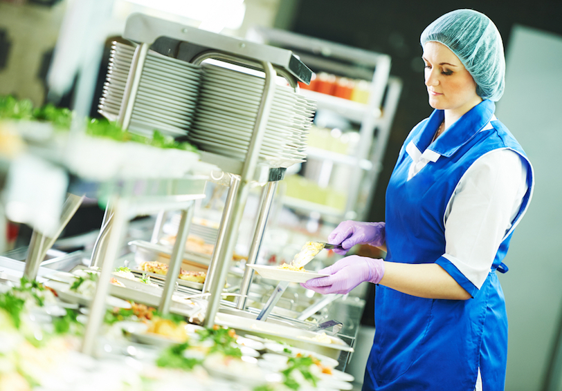 Female cafeteria worker setting up salad bar