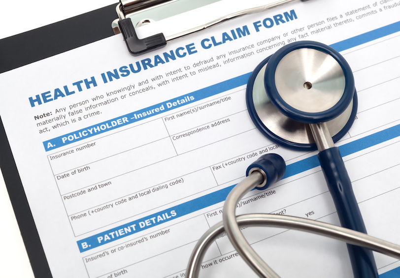 Health insurance claim form on a clipboard and a stethoscope