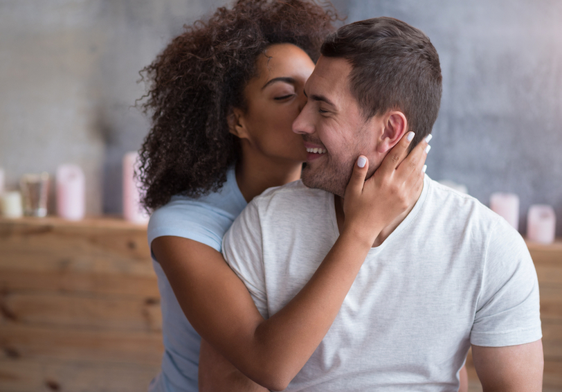 Woman kissing cheek of smiling man