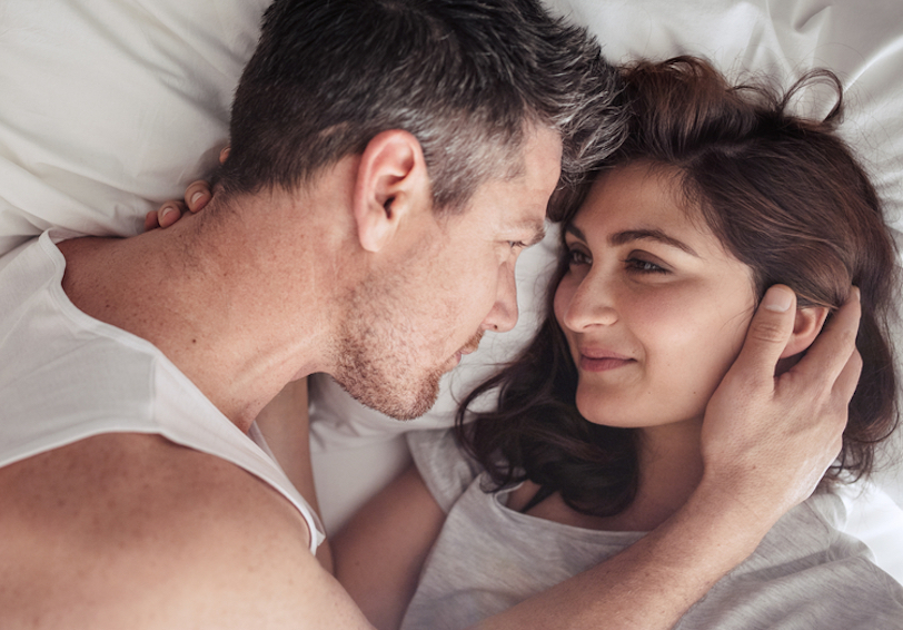 Couple lying in bed looking into each other's eyes