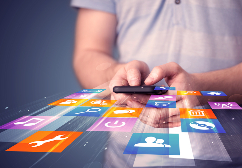 Man holding smart phone with colorful application icons coming out