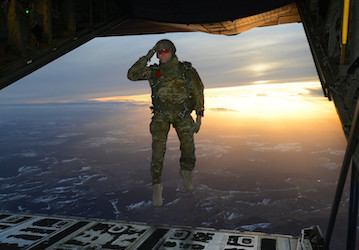 Soldier salutes while jumping out of aircraft U S  Army photo by Visual Information Specialist Jason Johnston Released