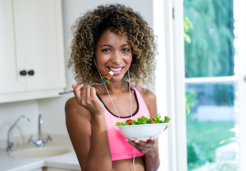 Woman eating healthy salad in workout clothes