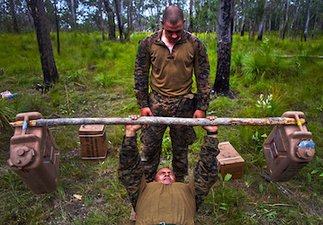 Marines use an improvised bench press with 40-pound water jugs. U.S. Marine Corps photo by Sgt. Jonathan Wright/Released