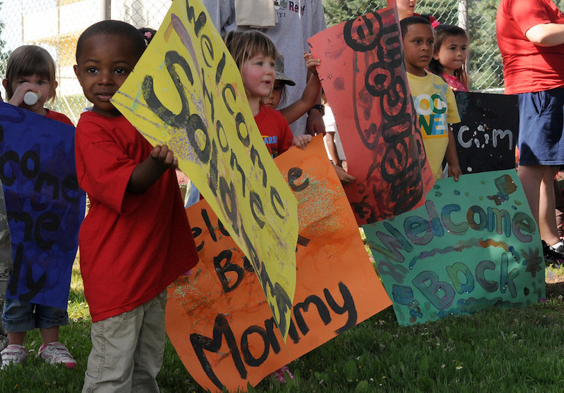 "Children holding ""welcome home"" signs (U.S. Air Force photo/Senior Airman Ashley Wood)"