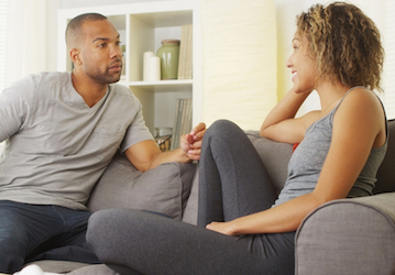 Man and woman sitting on couch facing each other having a conversation