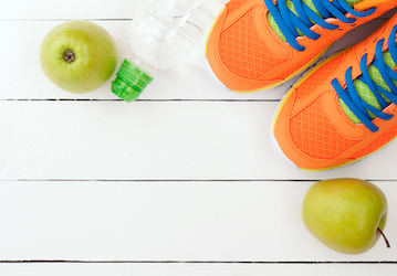 Running shoes, apples, and bottle of water on white floor