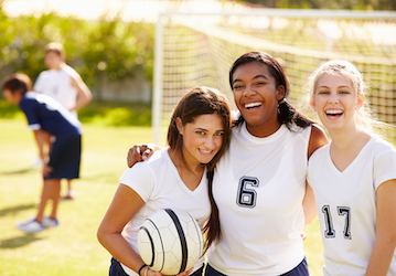 Three girls in soccer uniforms smiling and laughing