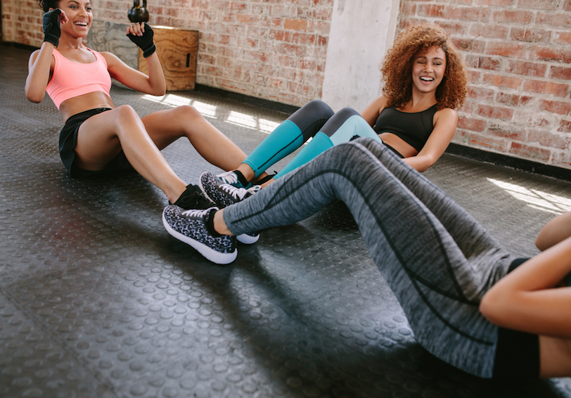 Group of women doing sit ups together and laughing in gym