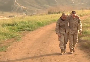 One soldier assisting another down a dusty sunny path