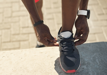 Foot and ankle of person tying shoe