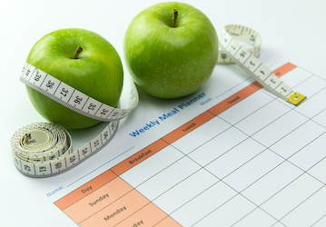 Apples and measuring tape sitting on paper with a weekly meal plan grid.