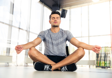 Man sitting on floor with crossed legs and closed eyes meditating