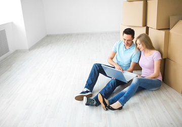 Man and woman sitting on floor talking and looking at computer next to stack of moving boxes in empty room