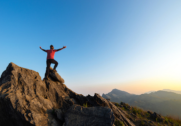 Person standing on mountain top with arms outstretched looking at view