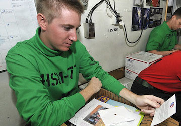 Sailor opens care package. (U.S. Navy photo by Mass Communication Specialist 1st Class Sarah Murphy/Released)