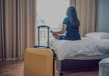 Woman meditating in a hotel room