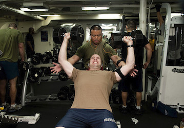Sailors lifting weights together in gym  U S  Navy photo by Mass Communication Specialist 3rd Class Kenneth Abbate Released