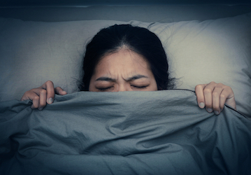 Woman in bed having a nightmare