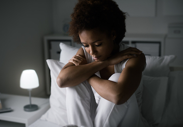 Sad looking woman sitting up in bed at night