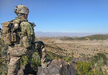 Soldier looking out over mountain valley  U S  Army photo by Sgt  1st Class Abram Pinnington Released