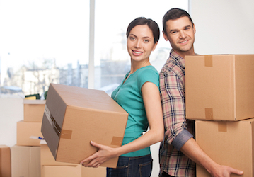 Man and woman holding boxes in room filled with boxes