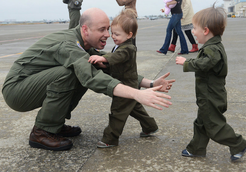 Servicemember greeting his children (U.S. Navy photo by Mass Communication Specialist 2nd Class Justin Smelley/Released)