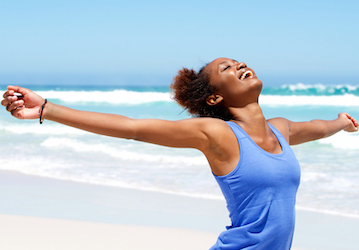 Smiling woman on beach with arms outstretched