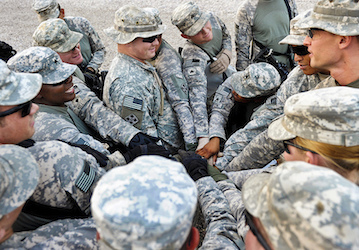 Group of soldiers in a circle putting their hands into the center  U S  Army Photo by Spc  Jason A Young