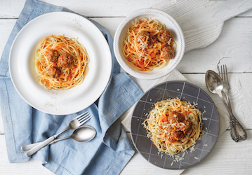 Three plates of spaghetti with meat balls on white wooden surface with cloth napkin and silverware
