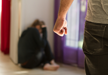 Woman sitting on floor with man standing over her making a fist.