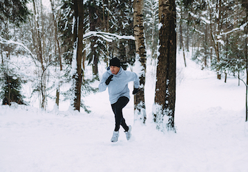 Man running up snowy hill