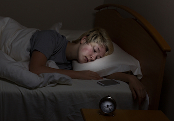 Teen boy sleeping in bed in dark room