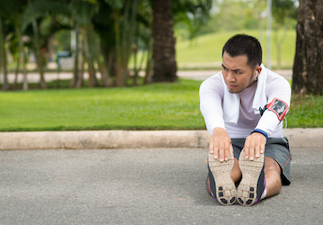 Man sitting on ground stretching
