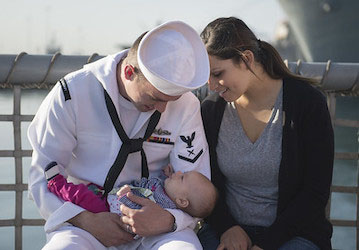 Seaman holds his baby daughter with his wife. (U.S. Navy photo by Mass Communication Specialist 3rd Class Cory Booth/Released)