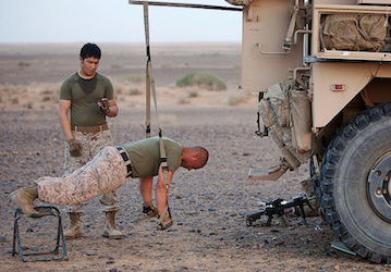 Marines working out using suspension straps on the back of a military vehicle (U.S. Marine Corps photo by Cpl. Alfred V. Lopez)