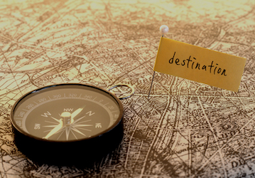 "Compass lying on a map with a pin marker with word ""destination"" on the marker"