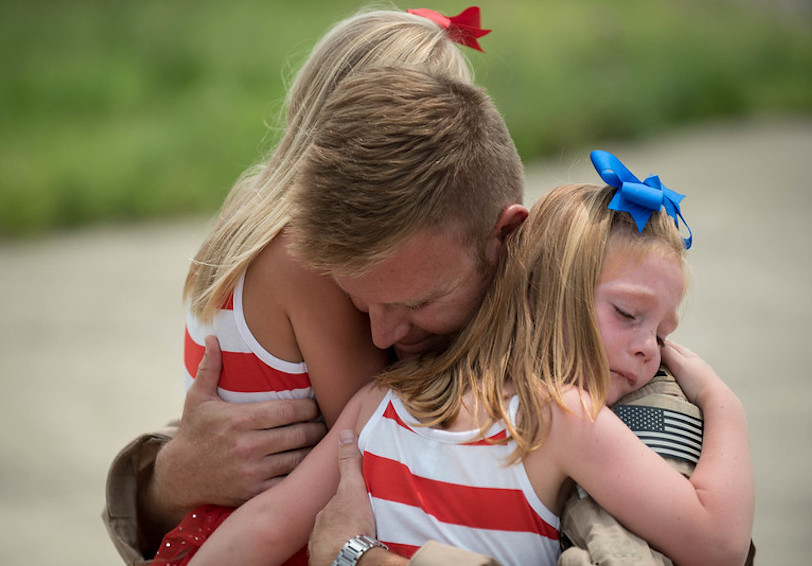 Airman hugging his daughters. (U.S. Air National Guard photo/Maj. Dale Greer)