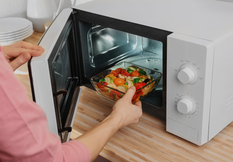 Woman microwaving healthy meal