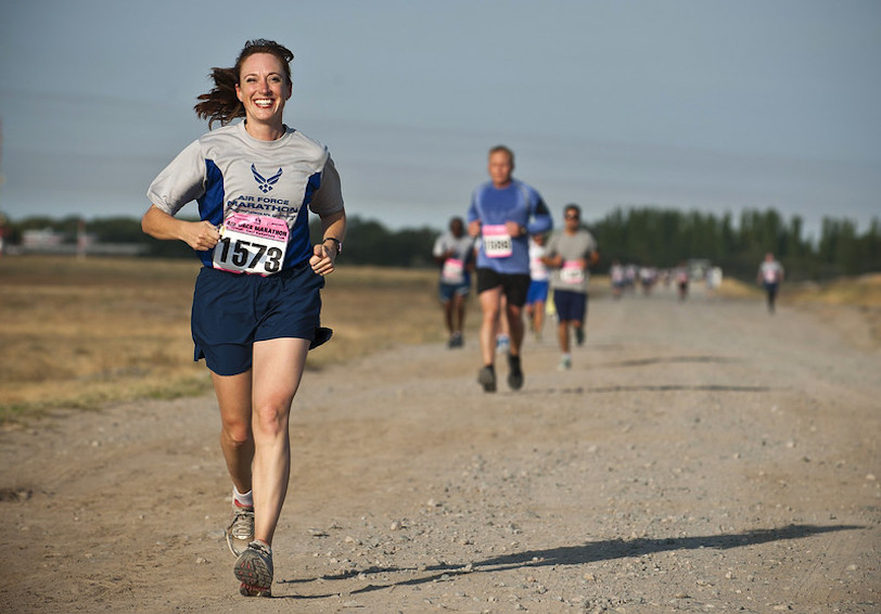 Smiling woman runs during the Air Force Marathon. (U.S. Air Force photo by Senior Airman Brett Clashman/Released)
