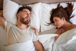 Frustrated woman in bed tries to wake her snoring bed partner.