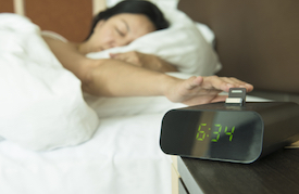 From her bed, woman sleepily reaches for alarm clock on nightstand.