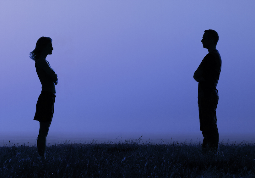 Silhouette of couple facing each other, arms crossed