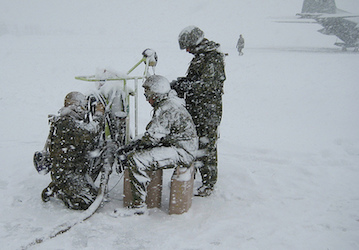 Airmen and Marines working on a snowy airfield (US Airforce photo)