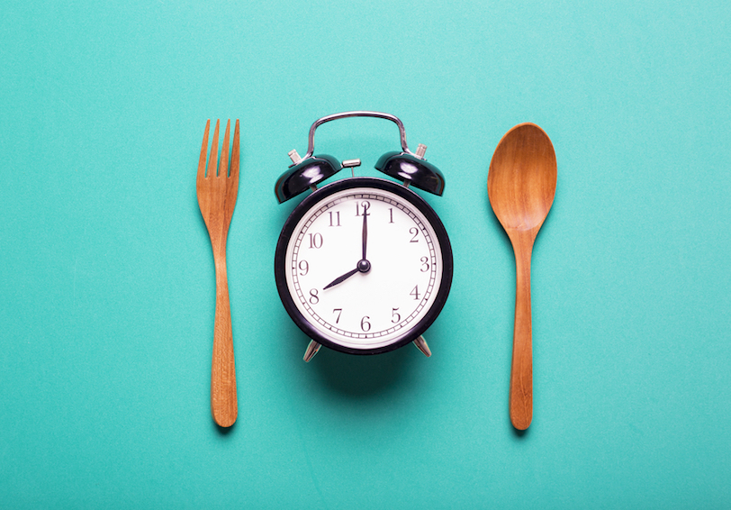 Fork, alarm clock, and spoon on blue background