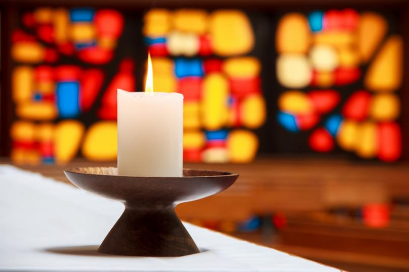 Candle with stained glass background