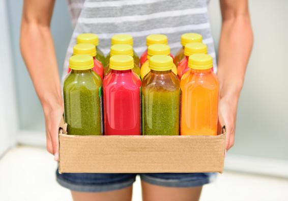 Woman holding box containing bottles of juice