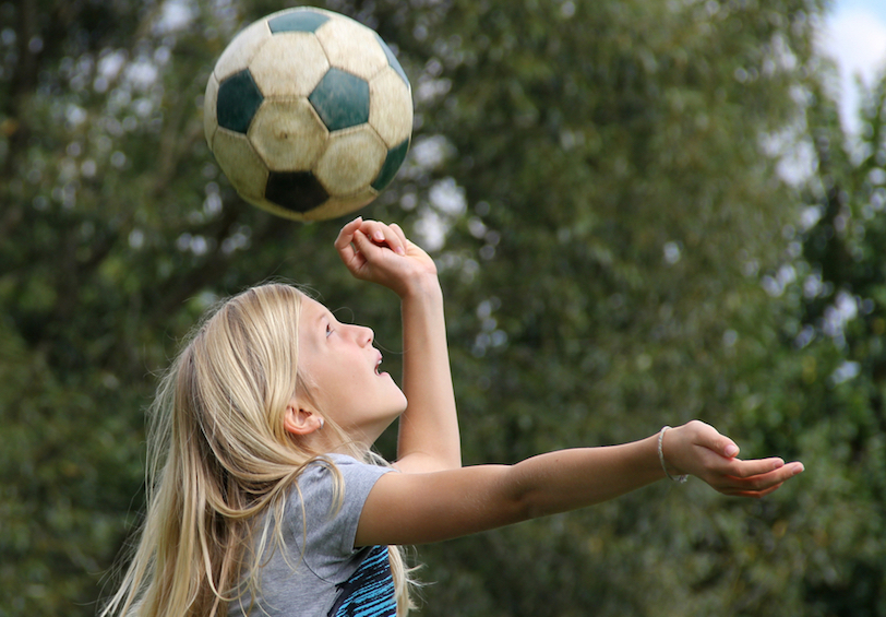 Young girl preparing to hit soccer ball with her head